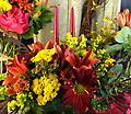 Joyful Celebrations - This 2 candle centerpiece will light up your table with orange lilies, rover mums, hypericum berries, yarrow, solidago and pomps.