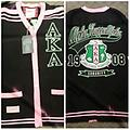 AKA Sweater - Front and back AKA pink and black sweater. AKA on the front. Pink and green patch on the one sleeve, and pearl leaf on the other sleeve. Alpha Kappa Alpha on the back 1908 with the shield and sorority