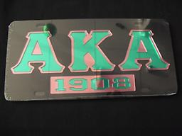 AKA black car tag with year and letters AKA black mirror car tag with the year in green