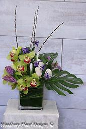Modern Orchids Fresh and modern cymbidium orchids with clematis, hyacinth, white iris and roses send an elegant wish for any occasion.