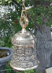 Carved Brass Bell Cast in pure brass, then intricately hand carved. Carvings of Hindu symbols decorate the sides and the top is a solid thick ring. Comes with a detailed chain and hook, and a functional clapper inside.