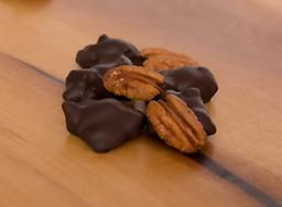 Dark Chocolate Covered Pecan Caramel Patties A luscious blend of soft, chewy caramel atop a mound of fresh roasted pecans drenched in dark chocolate.