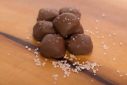Milk Chocolate Sea Salt Caramels A soft, chewy caramel center engulfed by rich milk chocolate, sprinkled with sea salt.