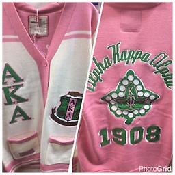 AKA 2016 Cardigan Sweater AKA pink and white cardigan sweater. From AKA letters and shield. Back: Alpha Kappa Alpha founders year and ivy leaf.