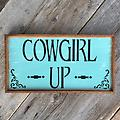 """Cowgirl Up, Western Signs and Home Decor, Country Signs, Indoor and Outdoor Signs, Farm and Ranch - The Cowgirl Up sign measures approx. 10.5"""" x 19.5"""". It has a distressed turquoise background with black lettering and stencils. Western Signs and Home Decor, Wood Wall Signs, Country, Barn Signs"""