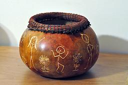 Stick Figure Bowl A bowl, made from a real gourd, with stick figures carved into it in a variety of positions. The bowl is topped with a rim of pine needles.