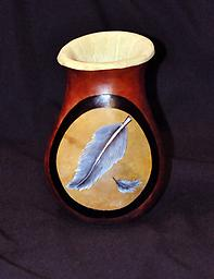 Feather Vase A small vase made from a gourd, with two gray feathers wood-burned onto it, against a background of mahogany.
