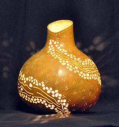 River Lantern A gourd drilled and carved so that it looks like a river of light circles around it.