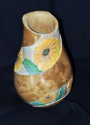 Daisy Vase A gourd vase with yellow daisies carved around the body.