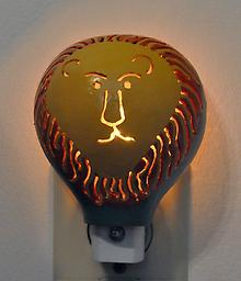 Lion Night Light A traditional night light with a lion-faced shield made made from a small gourd. Perfect for a child's room!
