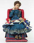 The Quilter - Miss Florence is surprised to see she has won a blue ribbon for her quilt. She is seated in her favorite sewing chair with her blue ribbon quilt on her lap.