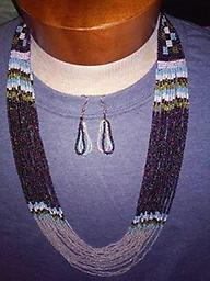 AWESOME NECKLACE/EARRINGS SET Beautiful beaded 16 strand necklace, opens to approximately 32 inches, multi-colored beads with matching 3 loop earrings 2 inches long. SET. Primary colors are blue, white, purple.