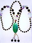 """""""Crystal, Lavender, & Green, Fit for a Queen"""" - This beautiful necklace has black and gold beads creating the over the head loop with crystal & lavender accents & an emerald green pendant with dangles adding 4 inches to the 29 inch loop."""