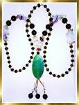 "#91 ""Crystal, Lavender, & Green, Fit for a Queen"" - This beautiful necklace has black and gold beads creating the over the head loop with crystal & lavender accents & an emerald green pendant with dangles adding 4 inches to the 29 inch loop."