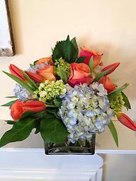 Splendid Day This brightly colored cube arrangement is sure to make everyone smile! Orange roses, orange tulips, with green and blue hydrangea are the perfect contrasting combination to lift your spirits.