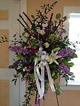 Shades of Purple Standing Spray - A thoughtful remembrance for that special someone. Displayed on a stand, this spray consists of stock, liatris, lilies, roses, hydrangea and orchids, fitting for a last tribute.
